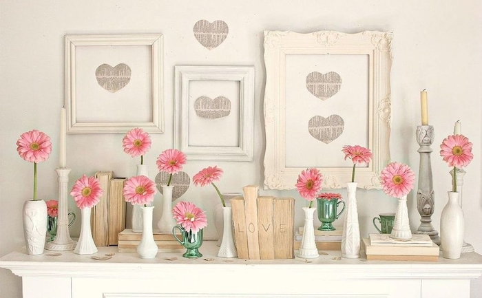 three vintage wooden frames, posters of hearts inside, valentine table decorations, pink flowers in separate vases