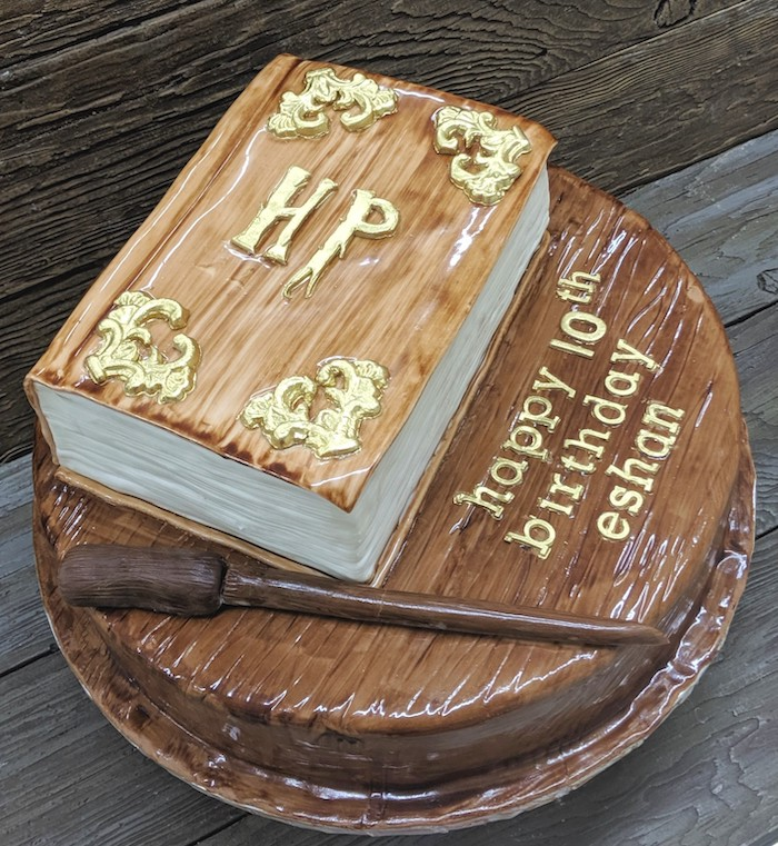 harry potter birthday cake hagrid, two tier cake, top tier in the shape of book, wand made of fondant on bottom layer