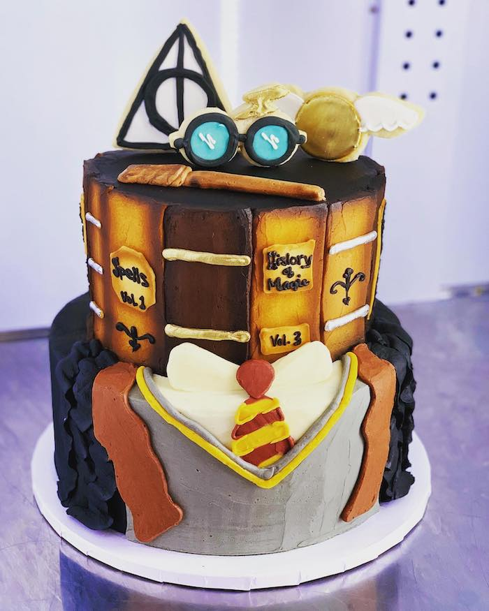 two tier gryffindor cake, harry potter birthday cake hagrid, gryffindor uniform bottom layer, glasses wand snitch on top