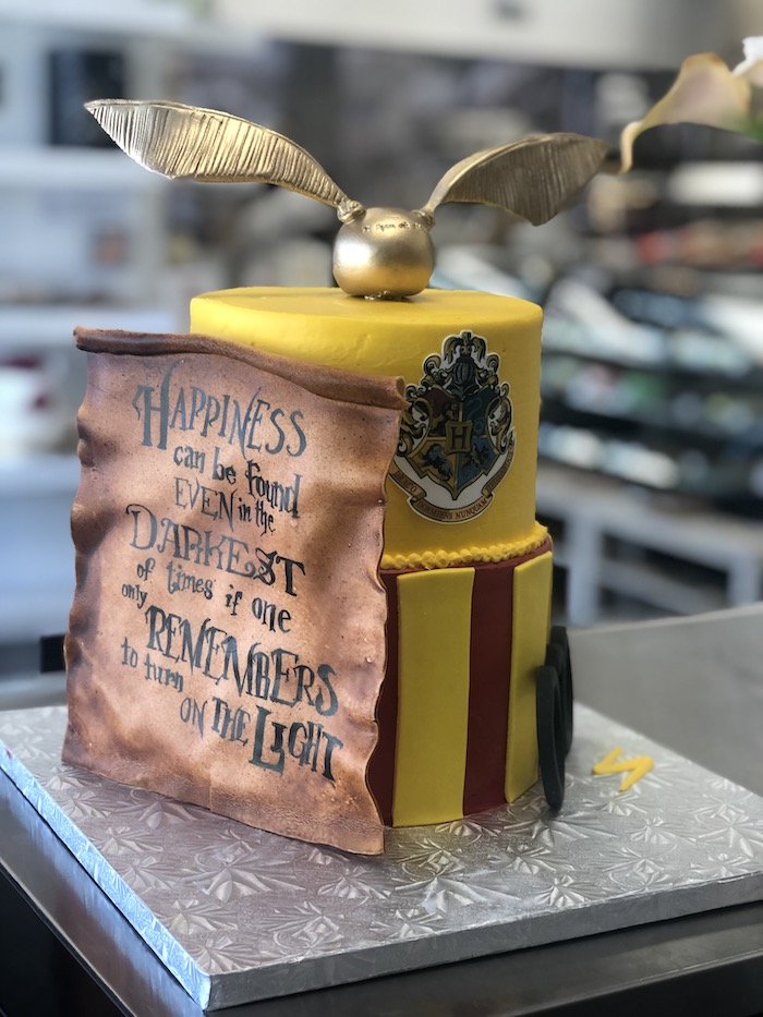 two tier gryffindor cake, made with yellow and red fondant, golden snitch on top, harry potter birthday cake hagrid