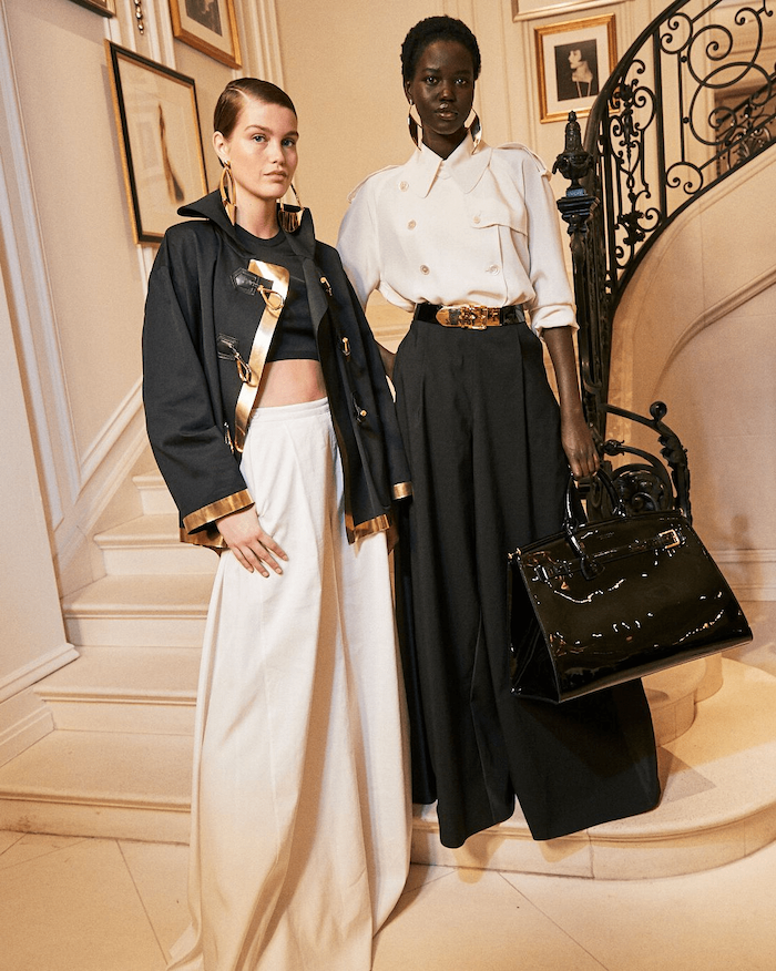 two women standing on staircase, valentines day clothes, dressed in black and white, wide pants and blazers