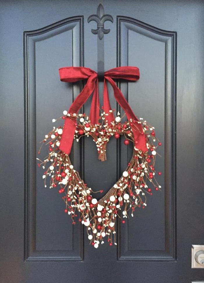 heart shaped wreath, made of twigs and faux berries, hanging on black door with red satin bow, valentines home decor