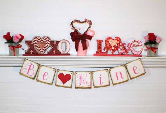 valentines home decor, be mine banner, hanging over white mantel, xoxo and love signs on top, small roses bouquets