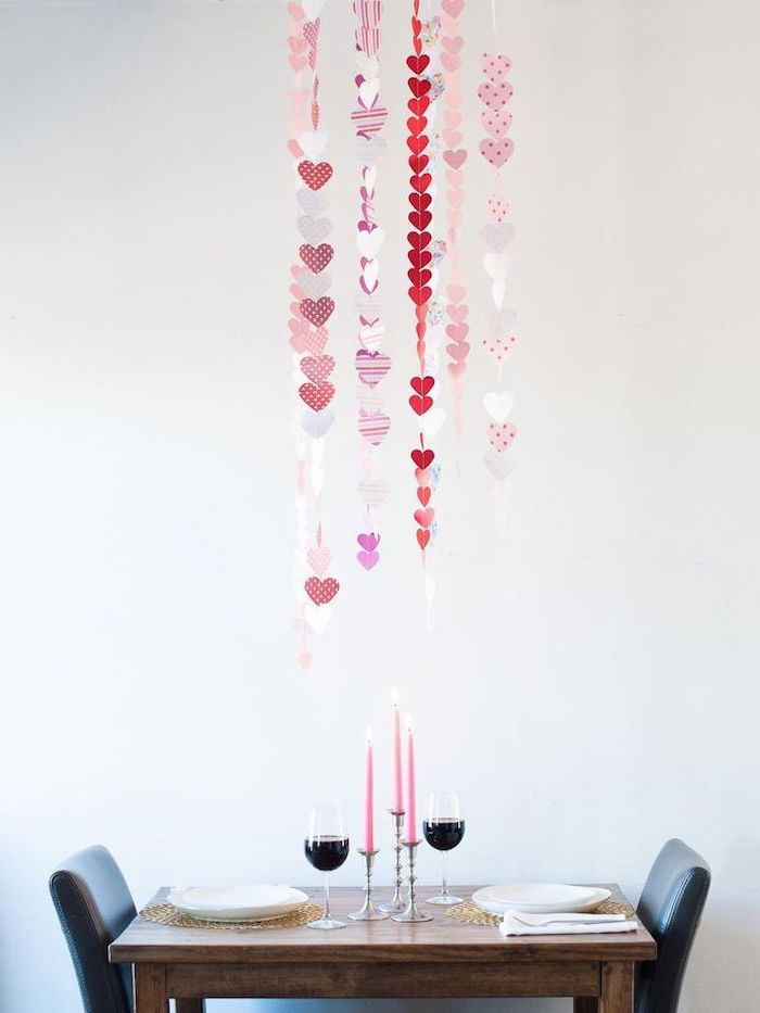 dinner table set for two, hearts garlands, hanging from the ceiling, valentines home decor, wine glasses and pink candles