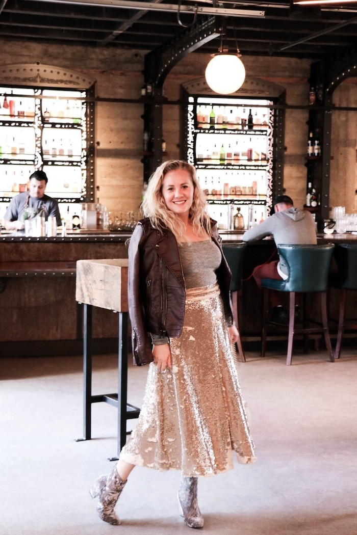 woman standing at a bar, wearing gold sequinned skirt, grey crop top and leather jacket, valentines day outfit girl