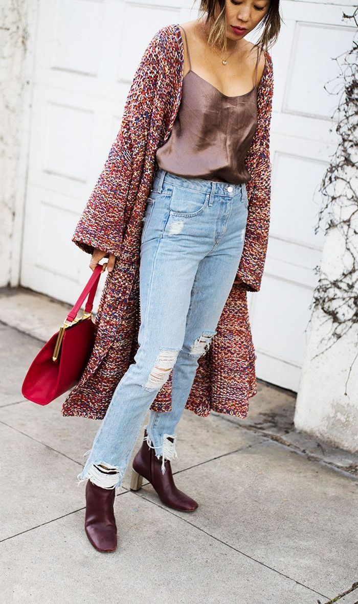 woman wearing brown top and jeans, long colorful knitted cardigan, valentines day outfit girl, red bag and burgundy boots