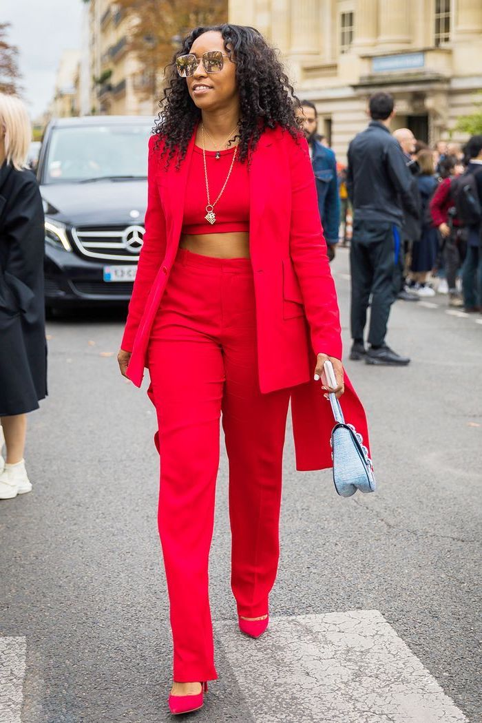 woman walking down the street, wearing red suit with crop top, valentines day outfit girl, red heels and blue bag