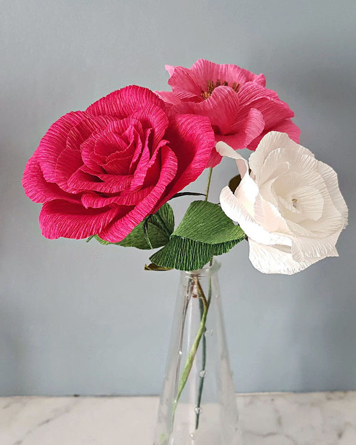 white and pink roses made of crepe paper, arranged as a bouquet, giant paper flower template, placed in small glass vase