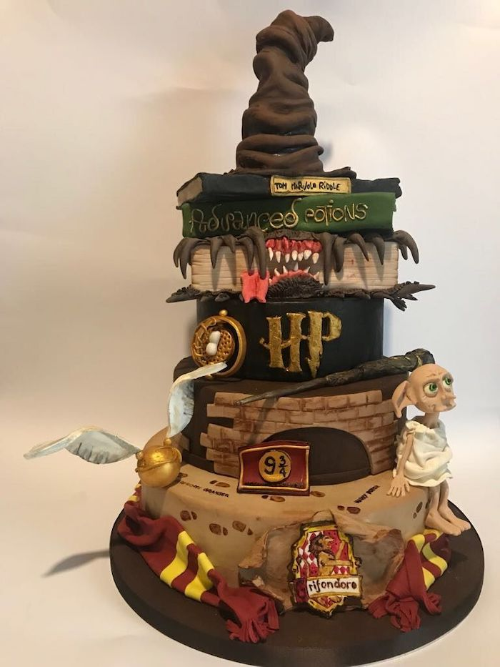 multi layered cake, sorting hat on top, wand dobby and golden snitch on the side, diy harry potter cake, gryffindor scarf around it