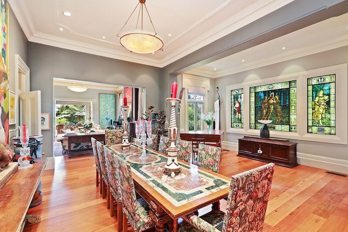 dining room with wooden floor, decorated large windows, stained glass window panels, vintage dining room and chairs