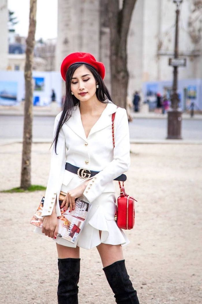 valentines day outfit ideas, woman wearing white dress with long sleeves, black velvet knee high boots, red bag and hat