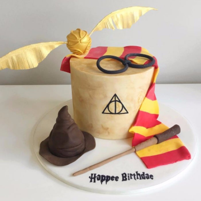 harry potter birthday cake ideas, one tier cake, gryffindor scarf made of red and yellow fondant, wand and snitch