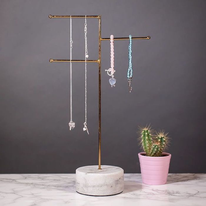 jewelry stand made from white marble and brass, unique valentines day gifts, placed on marble surface, potted cactus on the side