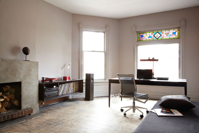 home office with wooden floor, two windows, custom stained glass, black wooden desk, shelves and fireplace
