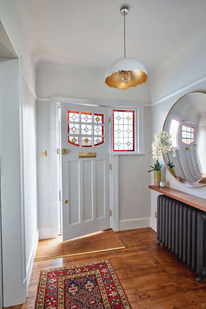 white front door decorated with stained glass, custom stained glass, hallway with wooden floor, large mirror on the white wall