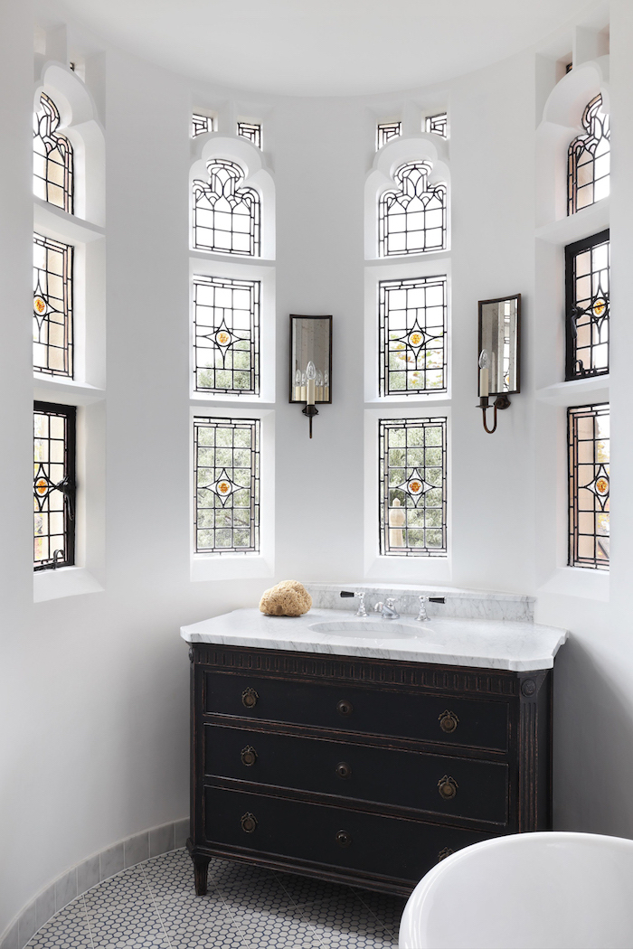 bathroom with white walls, dark wooden cupboard, marble countertop sink, how to make stained glass windows, tall and narrow windows