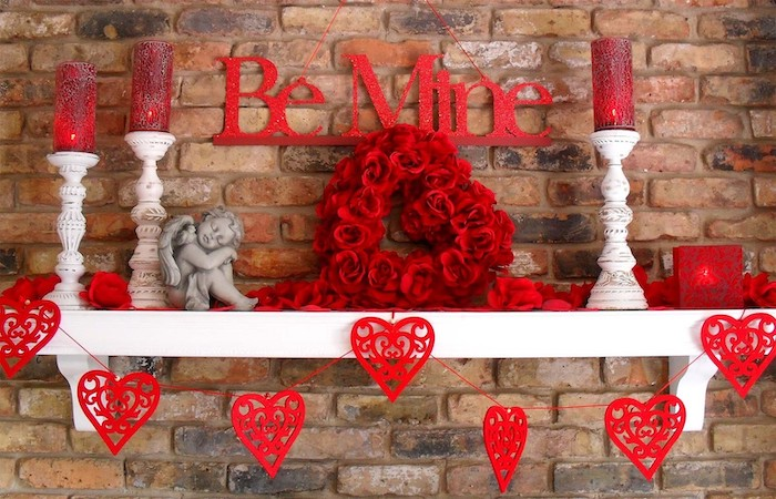 be mine banner, red hearts garland, vintage candlesticks, arranged on white shelf, valentine day table decorations, brick wall