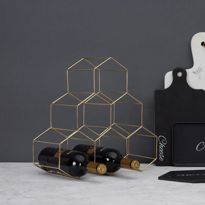wine rack made of six brass hexagonal shapes, valentine gifts for wife, two bottle on the rack, placed on marble surface