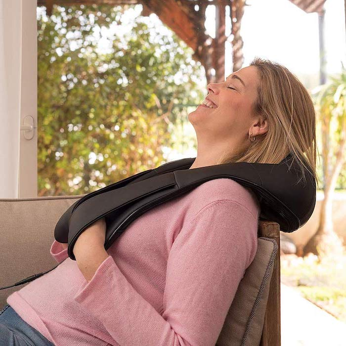 woman lying on a sofa, wearing a pink sweater, valentine gifts for wife, using a shiatsu neck and back massager