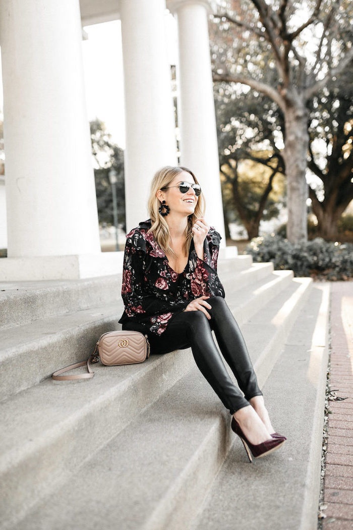 woman sitting on stairs, valentines day outfit ideas, wearing black leather pants, floral blouse and sunglasses