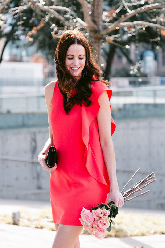 woman holding a bouquet of pink roses, wearing red dress, valentines day outfit ideas, small black clutch bag
