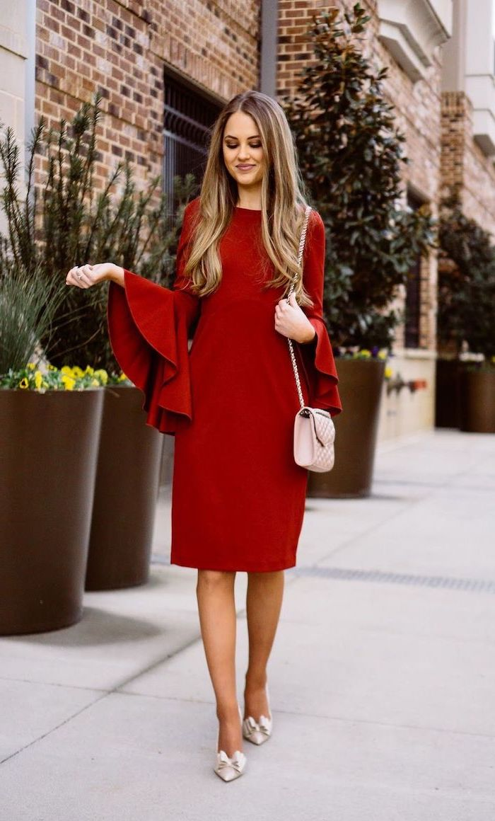 woman walking on sidewalk, wearing red dress with wide ruffled sleeves, valentines day outfit ideas, pink bag