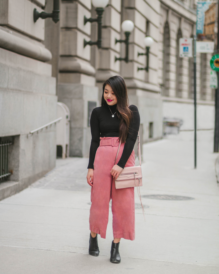woman wearing black polo blouse, pink wide pants, black leather boots and pink bag, cute valentines day outfits