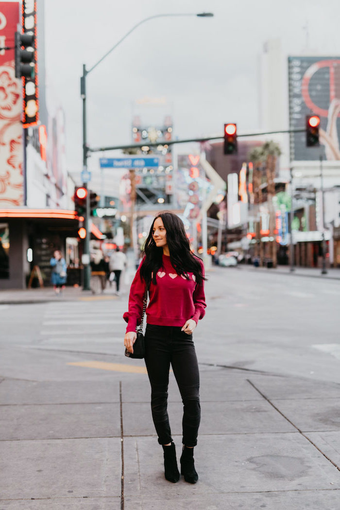 woman standing on sidewalk, wearing pink blouse, cute valentines day outfits, black pants and black velvet boots