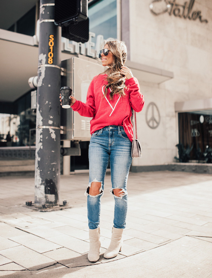blonde woman wearing jeans and red blouse, cute valentines day outfits, white leather boots, holding coffee cup