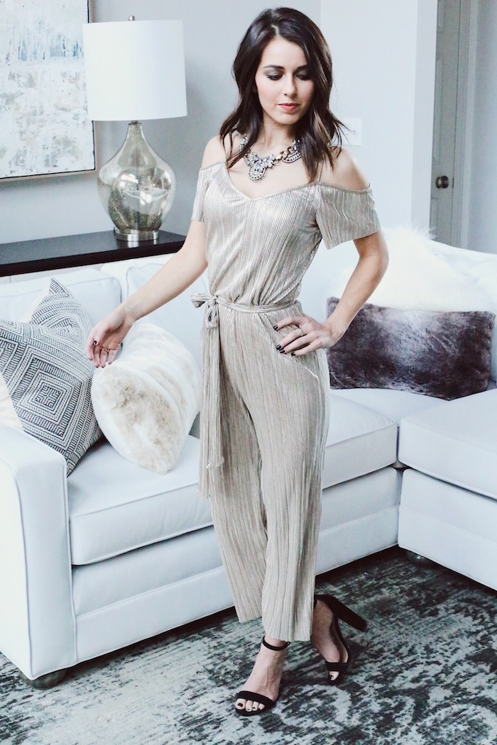 what to wear on valentine's day, woman standing next to white sofa, wearing silver jumpsuit, black sandals