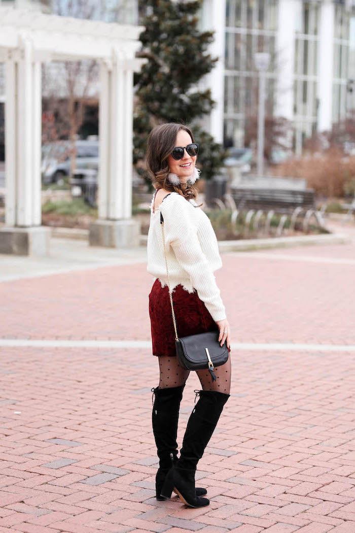 woman standing on sidewalk, what to wear on valentine's day, wearing red velvet skirt, white sweater, black boots and bag
