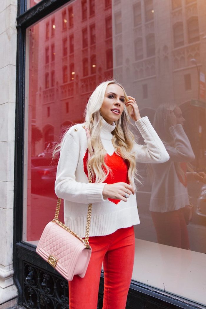 blonde woman wearing white sweater, with large red heart in the middle, what to wear on valentine's day, red pants, pink bag