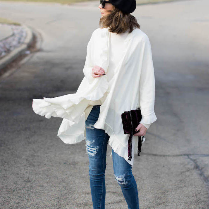 woman wearing jeans, what to wear on valentine's day, white blouse and kimono, holding black clutch bag