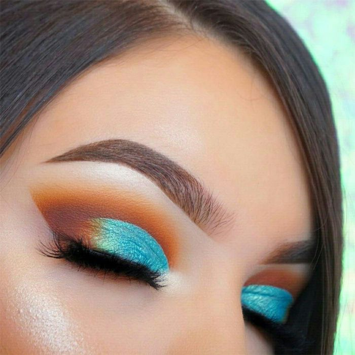 orange and turquoise eyeshadow colors, woman with brown hair, brown thick eyebrows, gold smokey eye