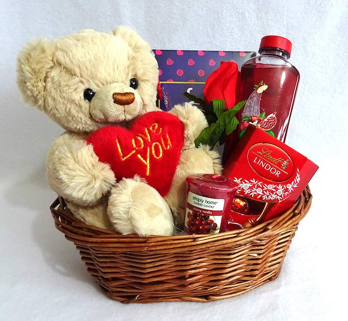 wooden basket, filled with candies and plush teddy bear, valentine's day gift ideas for her, placed on white surface