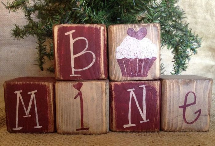 be mine wooden cubes, painted in red, valentine day table decorations, green tree branches in the background