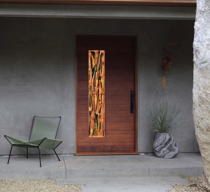 large wooden front door, decorated with stained glass, how to make stained glass windows, grey walls and chair next to the door