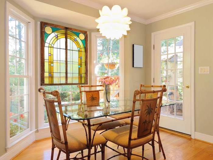 custom stained glass windows, dining room with wooden floor, glass table and wooden chairs, tall windows and door