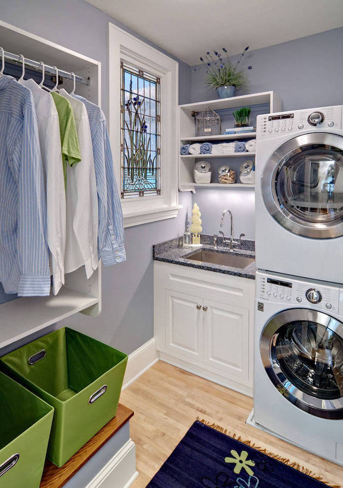 laundry room with wooden floor, custom stained glass windows, washing and drying machines, small window above the sink