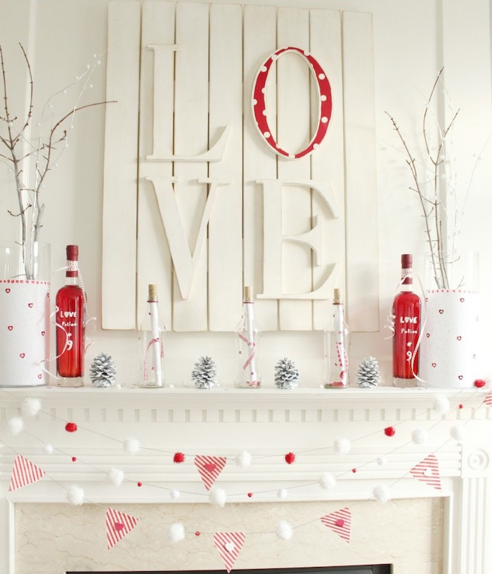white wooden love board, garlands hanging over mantel, bottles painted in red, pine cones, arranged on shelf, valentine day table decorations