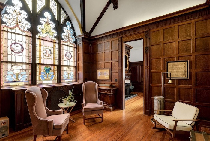 vintage style room, custom stained glass windows, cathedral ceiling and windows, wooden floor, two blush velvet armchairs