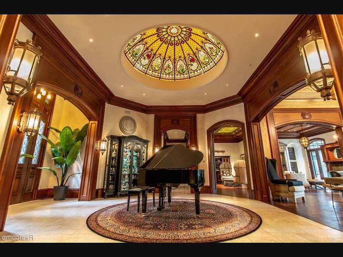 hallway with piano in the middle, wooden door frames, ceiling window, custom stained glass windows, white tiled floor