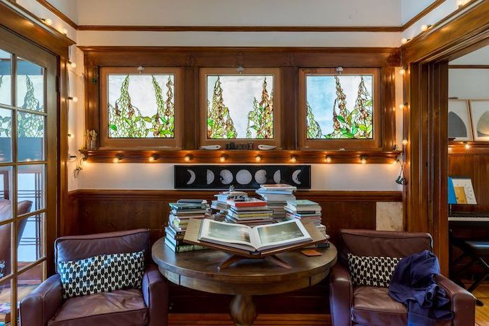 reading room with wooden window and door frames, custom stained glass windows, brown leather armchairs, round table with books