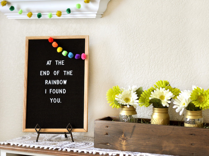 at the end of the rainbow i found you sign, rainbow pom poms garland on it, st patrick's day decorations, flower bouqets