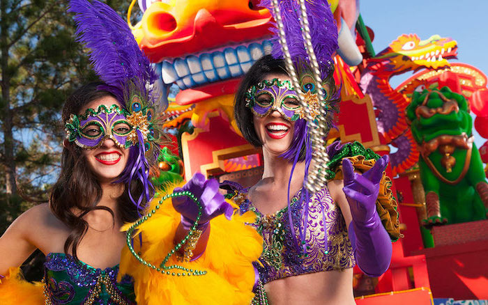 mardi gras mask, two women wearing mardi gras costumes, throwing beads at the carnival, masks with large feathers
