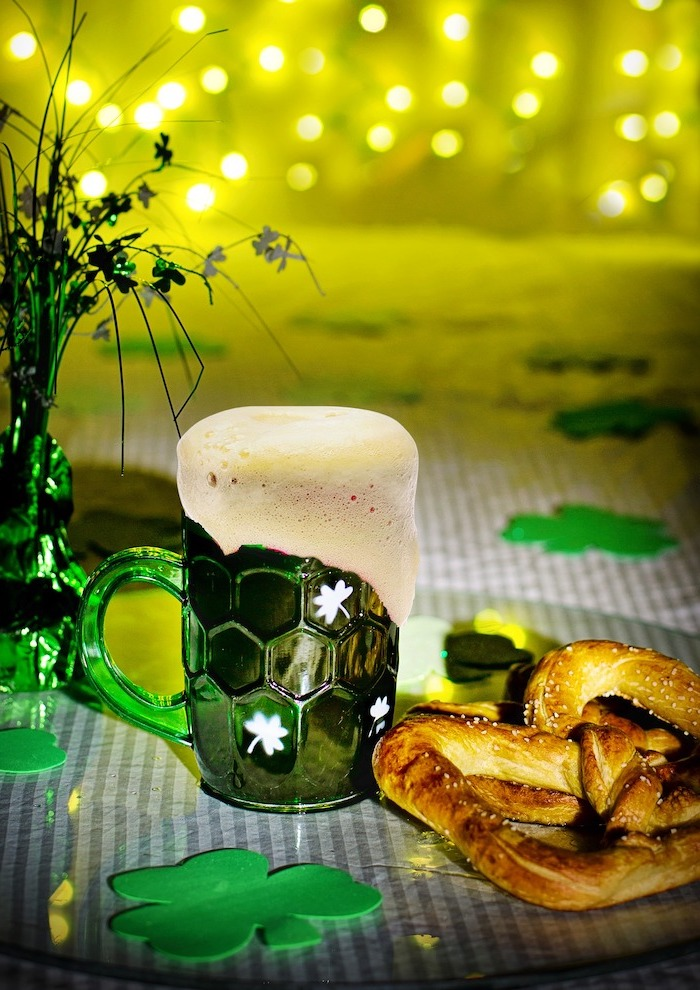 beer in green mug with white shamrocks, placed on a table, st patrick's day decorations, fairy lights in the background