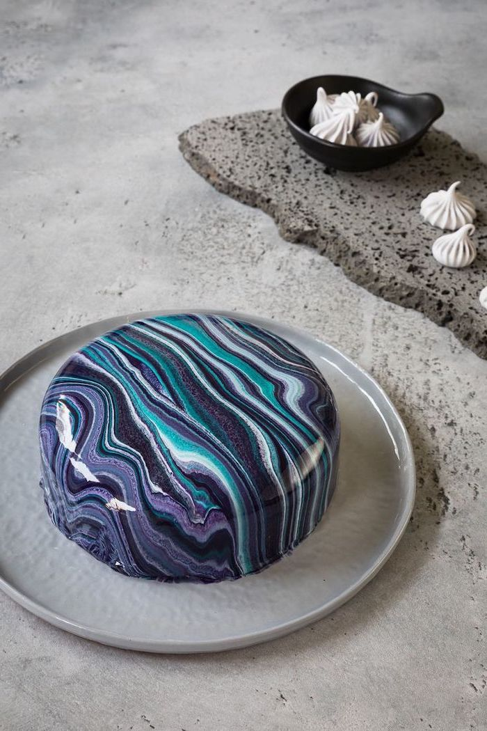 mirror glaze cake, blue purple and white glaze on one tier cake, placed on grey cake tray, meringue kisses in a a bowl