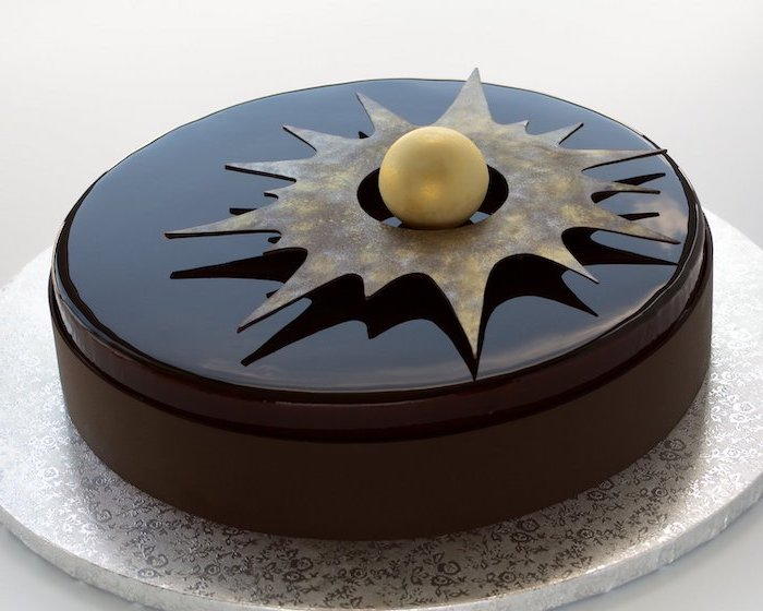 one tier cake with black brown glaze, mirror glaze cake, gold decorations on top, placed on silver cake tray