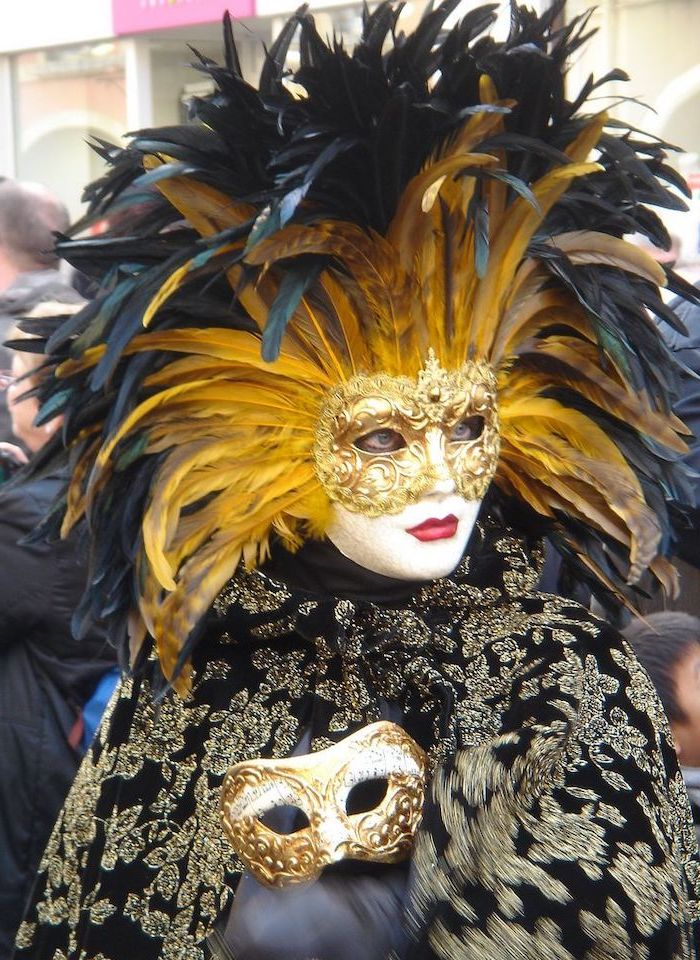 woman wearing a black and gold velvet cape, golden mask with large gold and black feathers, masquerade masks for couples