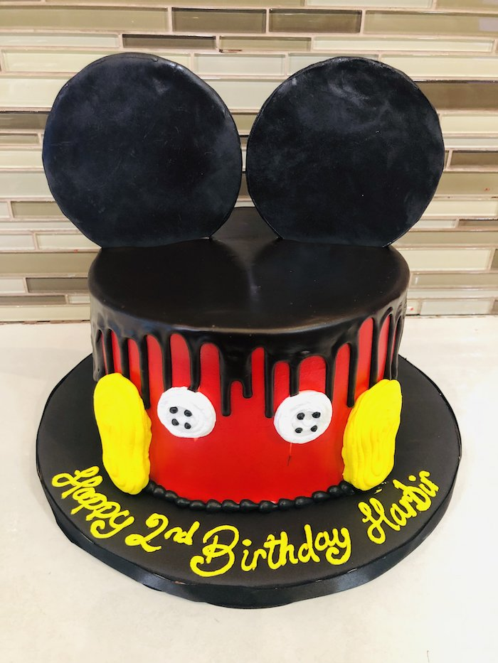 one tier cake, covered with red fondant, black fondant dripping from the sides, mickey mouse clubhouse cake